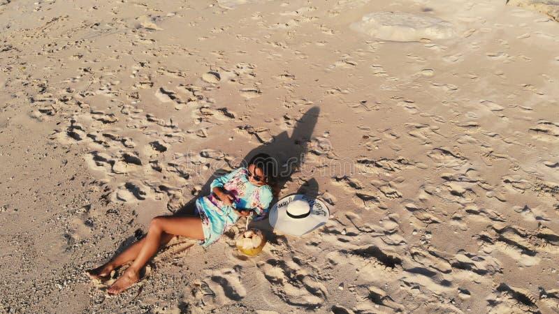 Vue aérienne de bourdon de jeune femme de brune dans des lunettes de soleil se trouvant à la plage de paradis et au téléphone por photo libre de droits