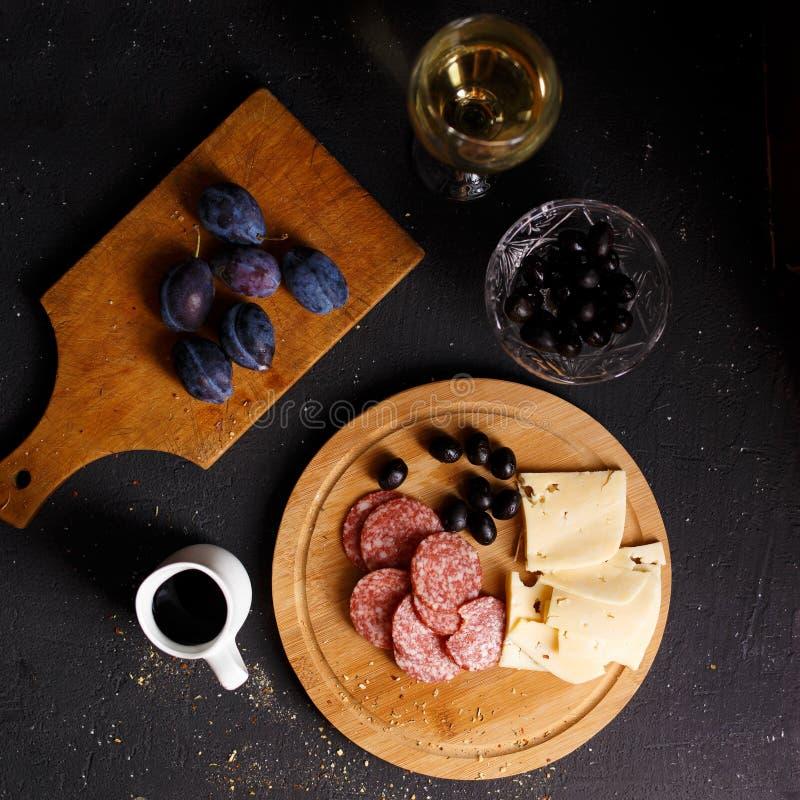 Vue aérienne de casse-croûte de viande de table d'apéritif, de saucisses frites, de fromage, de salami, d'olives et d'un verre de images libres de droits