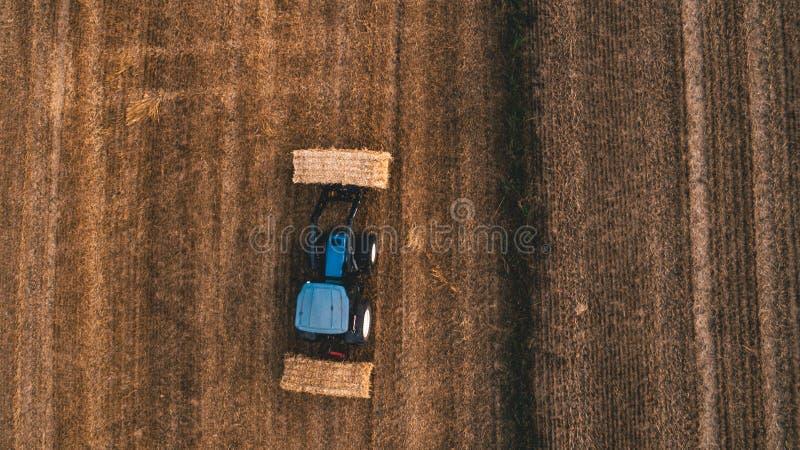 Vue aérienne de champ de récolte avec la balle de foin mobile de tracteur autour images libres de droits