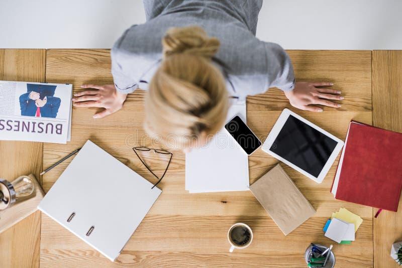 vue aérienne de femme d'affaires se penchant sur le lieu de travail avec les dispositifs numériques images libres de droits