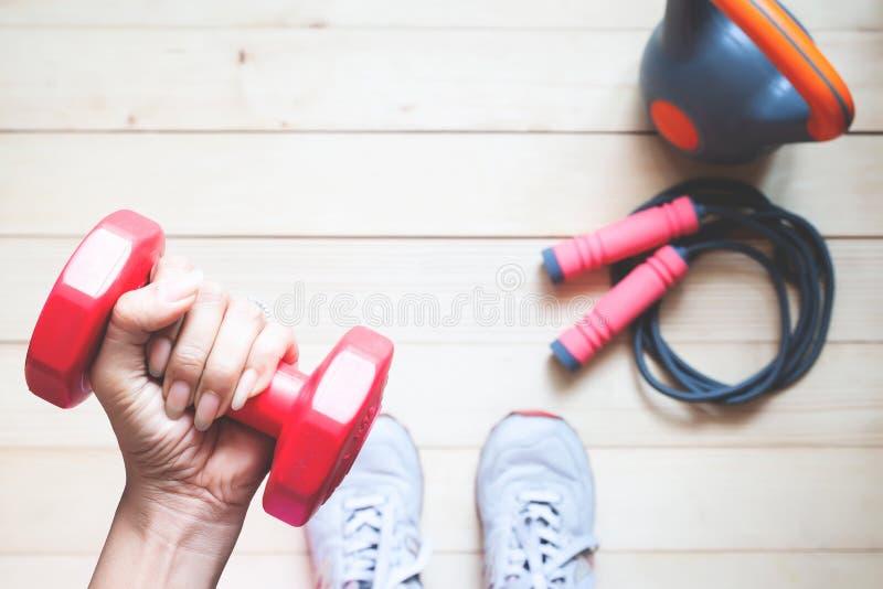 Vue aérienne de fille de forme physique tenant l'haltère rouge avec des équipements de forme physique sur le plancher en bois Sai photographie stock