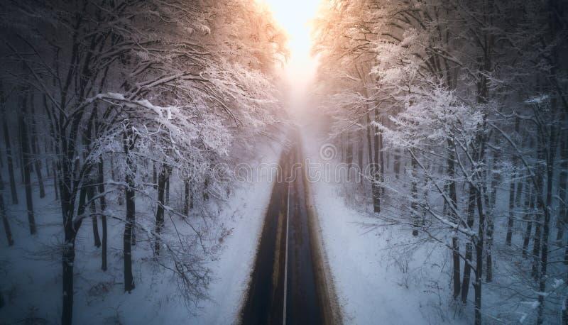 Vue aérienne de forêt neigeuse avec une route au coucher du soleil Capturé de ci-dessus avec un bourdon Carpathiens, Roumanie images stock