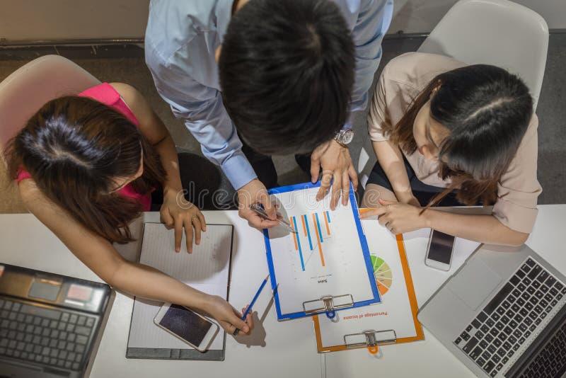 Vue aérienne de foyer de trois entrepreneurs sur le rapport photo stock
