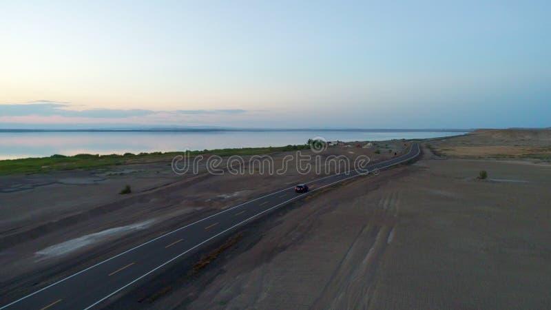 Vue aérienne de la conduite pendant le coucher du soleil sur une route vide au milieu du désert photo stock