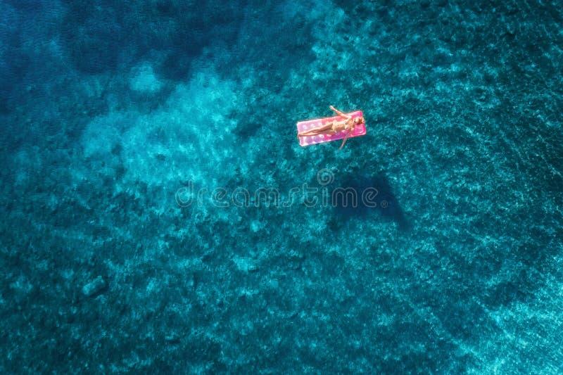 Vue aérienne de la natation de jeune femme sur le mattr gonflable rose photographie stock