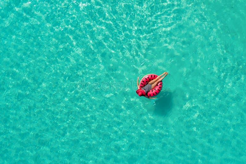 Vue aérienne de la natation mince de femme sur l'anneau de bain dans le transport photos stock