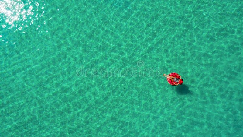 Vue aérienne de la natation mince de femme sur le beignet d'anneau de bain en mer transparente de turquoise en Seychelles Paysage photos libres de droits