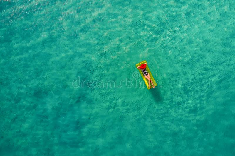 Vue aérienne de la natation mince de femme sur le matelas de bain dans le t image stock