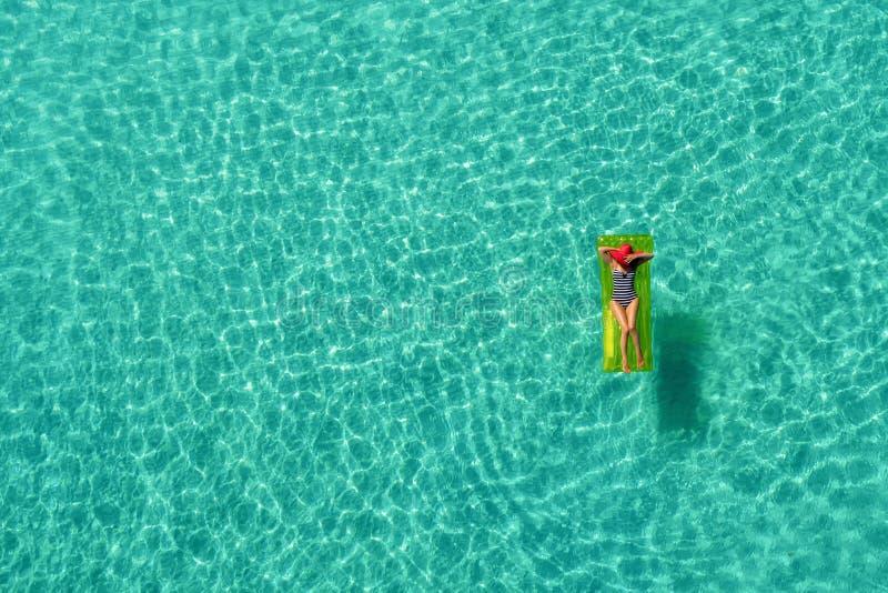Vue aérienne de la natation mince de femme sur le matelas de bain dans le t images libres de droits