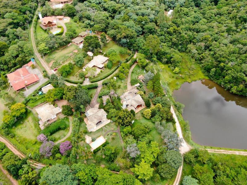 Vue aérienne de paysage de vallée verte dans le pays tropical avec la forêt, champ de ferme et entouré par la villa riche de luxe photo libre de droits