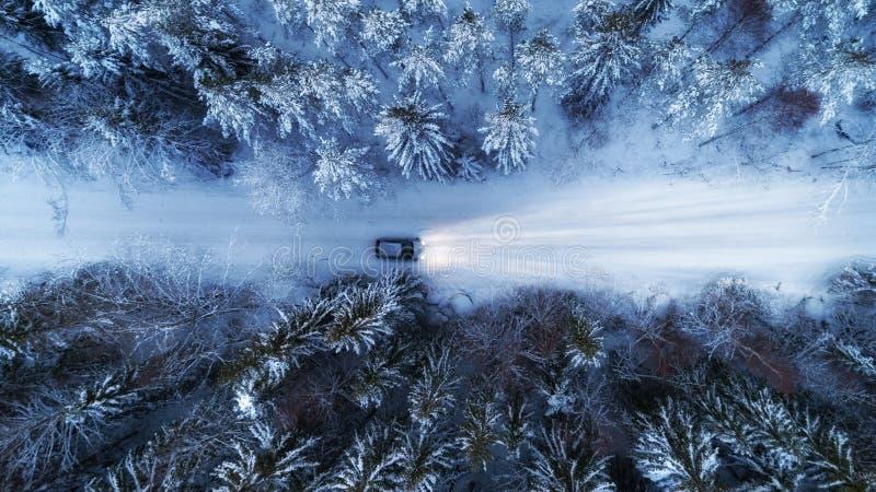 Vue aérienne de route et de voiture d'hiver de nuit dans le tir de bourdon de forêt photos stock