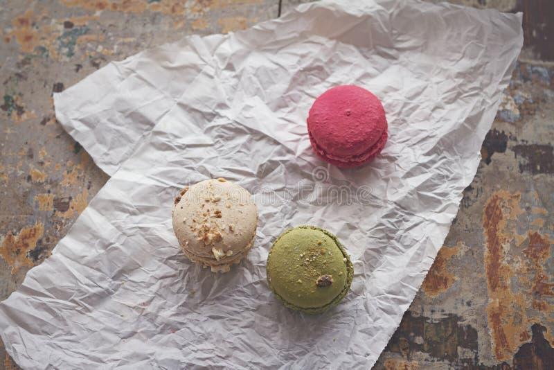 Vue aérienne de trois macarons délicieux sur le papier chiffonné photos stock