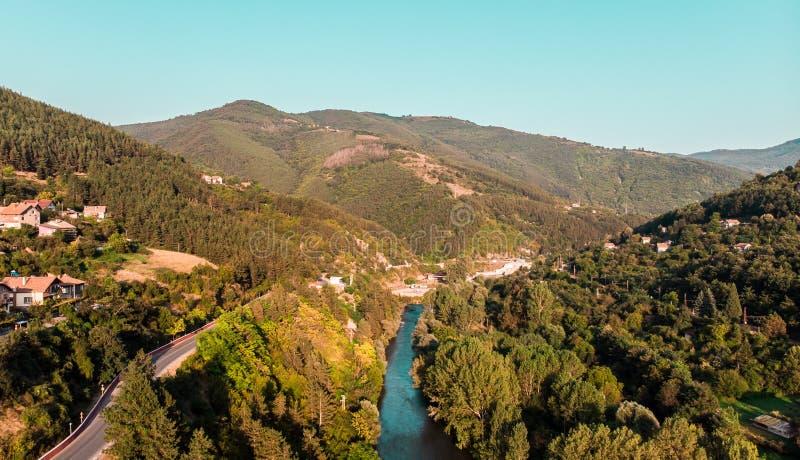 Vue aérienne de village rural d'une rivière en Bulgarie entre les montagnes Image par le bourdon photo libre de droits