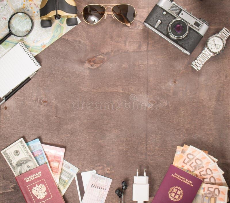 Vue aérienne des accessoires, des passeports et des billets de banque du ` s de voyageur Concept de voyage sur le fond en bois L' photographie stock libre de droits