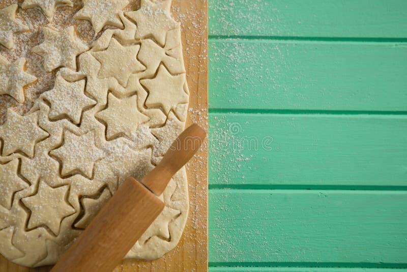 Vue aérienne des biscuits de forme d'étoile sur la pâte et du roulement sur la planche à découper image libre de droits