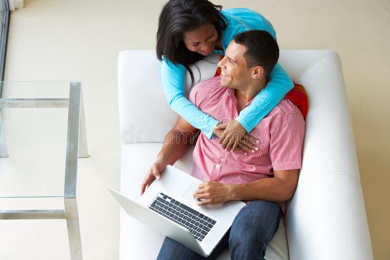 Vue aérienne des couples détendant sur Sofa Using Laptop photos stock