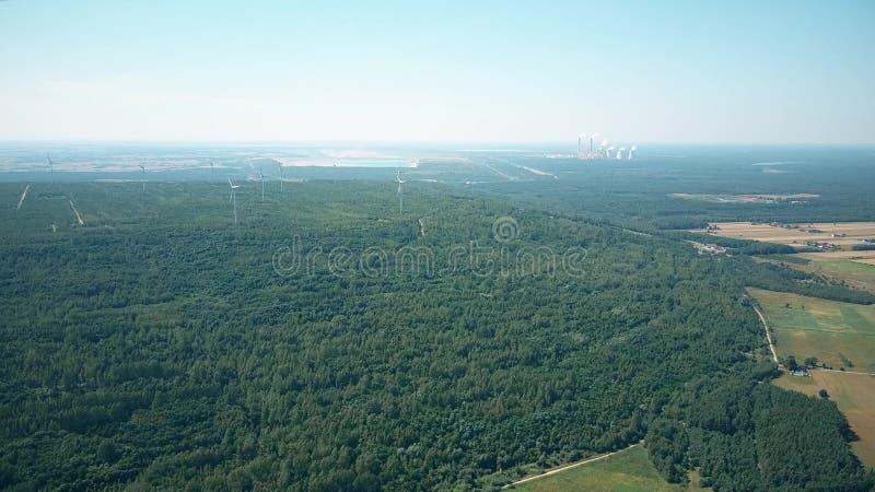 Vue aérienne des générateurs de vent contre les cheminées d'évacuation des fumées d'une centrale traditionnelle Production énergé photographie stock libre de droits