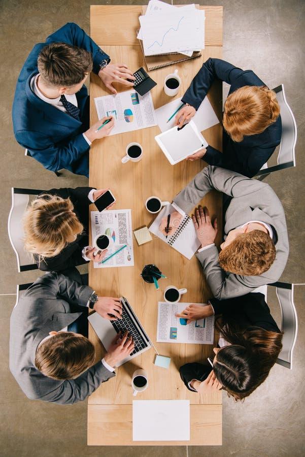 vue aérienne des hommes d'affaires discutant à la table avec les tasses de café numériques de dispositifs photographie stock libre de droits