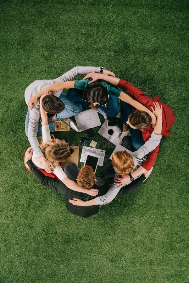 vue aérienne des hommes d'affaires embrassant tout en se reposant sur l'herbe avec des dispositifs image libre de droits