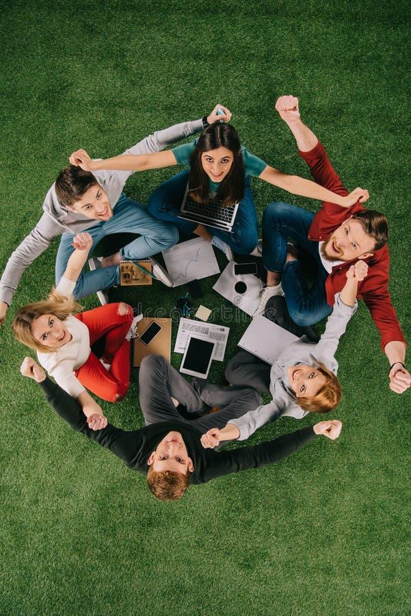 vue aérienne des hommes d'affaires heureux avec des bras vers le haut de se reposer photos stock