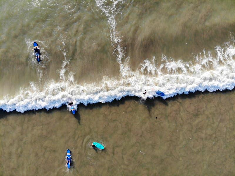 Vue aérienne des surfers attendant les vagues dans l'eau brune foncée dans Bali, Indonésie photographie stock libre de droits