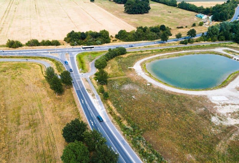 Vue aérienne du confluent de deux routes de campagne à côté d'une nouveauté avec un bassin de conservation de pluie images libres de droits