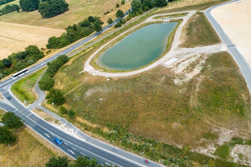 Vue aérienne du confluent de deux routes de campagne à côté d'une nouveauté avec un bassin de conservation de pluie photo stock