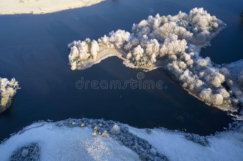 Vue aérienne du givre de Hoar et du lac gelé de l'eau de glace et des nuages de faible brouillard en hiver dans Loch Dochart Scot photos libres de droits