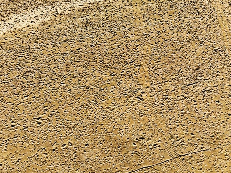 Vue aérienne du sable de rose de désert d'aridité clouté avec des empreintes de pas et des voies de pneu images libres de droits