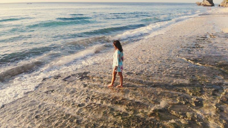Vue aérienne idyllique de bourdon de la jeune femme réfléchie se tenant sur la plage observant la vue scénique du paysage marin p image stock