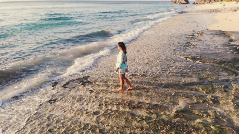 Vue aérienne idyllique de bourdon de la jeune femme réfléchie se tenant sur la plage observant la vue scénique du paysage marin p photographie stock