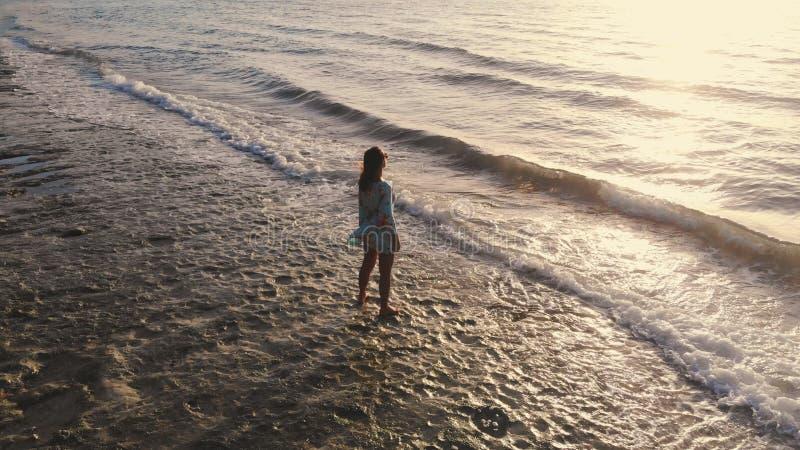 Vue aérienne idyllique de bourdon de la jeune femme réfléchie se tenant sur la plage observant la vue scénique du paysage marin p photos libres de droits
