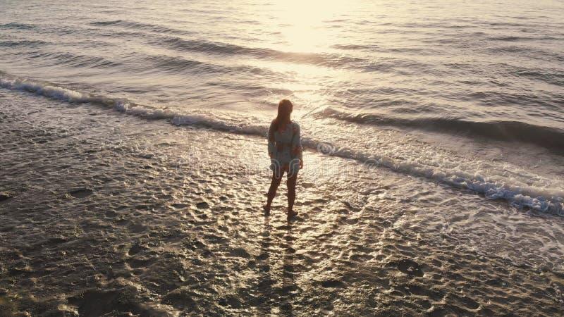Vue aérienne idyllique de bourdon de la jeune femme songeuse se tenant sur la plage observant la vue scénique du paysage marin pe photographie stock