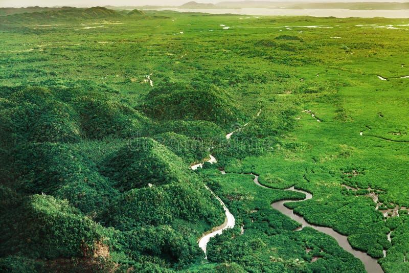 Vue aérienne sur le beau coucher du soleil au-dessus des montagnes et de la forêt tropicale de palétuvier vert en île de Siargao, photographie stock libre de droits