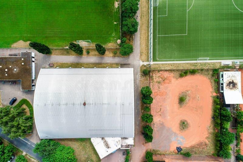 Vue aérienne verticale d'un hall de tennis à côté d'un terrain de football vert avec l'herbe devant un gisement de cendre rouge à image stock