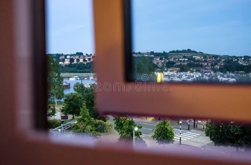 Vue abstraite d'une fenêtre partiellement ouverte d'hôtel, regardant à une rivière anglaise célèbre pendant le crépuscule photos stock