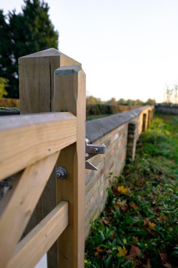 Vue abstraite d'une nouvelle porte de structure de bois vue à la frontière d'un petit cimetière de village images stock