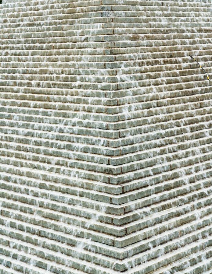Vue abstraite d'une pyramide artsy de fontaine d'eau avec de l'eau coulant et s'écoulant goutte à goutte vers le bas images stock