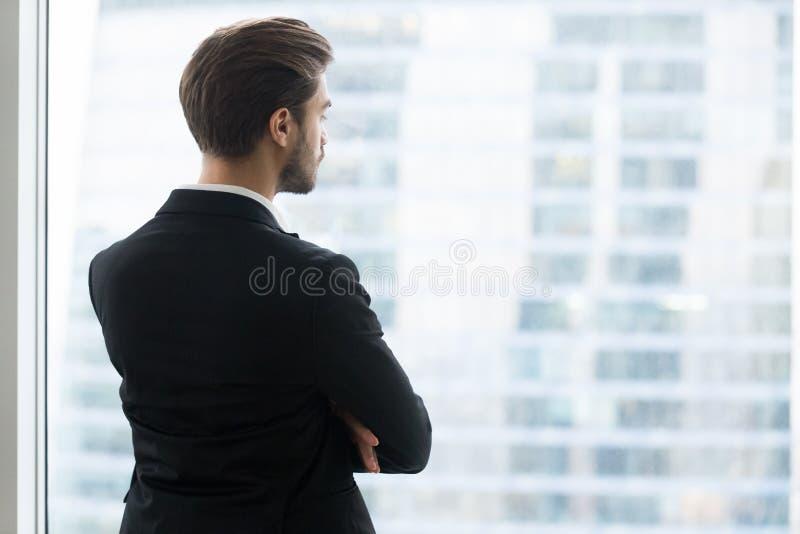 Vue arrière à l'homme d'affaires regardant par la fenêtre la ville moderne photographie stock libre de droits