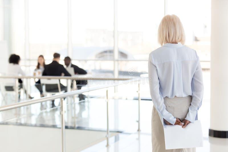 Vue arrière à la femme d'affaires supérieure nerveuse soumise à une contrainte I de attente images stock