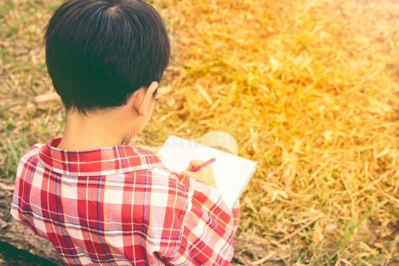 Vue arrière Écriture de garçon sur le livre réserve vieux d'isolement par éducation de concept Type de cru image libre de droits
