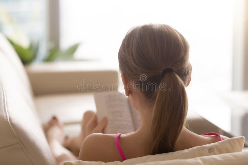 Vue arrière au livre de lecture de femme sur le divan à la maison images libres de droits