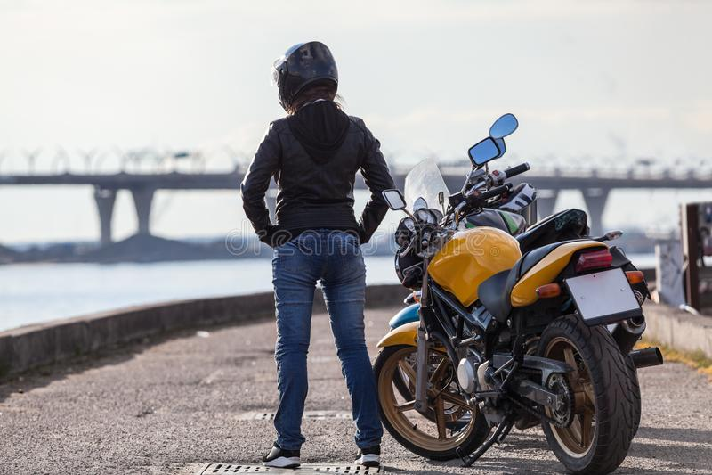 Vue arrière au motard de fille dans le casque de moto se tenant à côté des vélos sur le remblai de mer de rue, intégral photographie stock