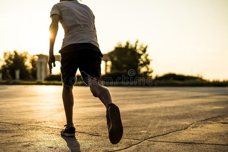 Vue arrière d'athlète de jeune homme en silhouette occasionnelle fonctionnant dans la ville urbaine sur un coucher du soleil photos stock