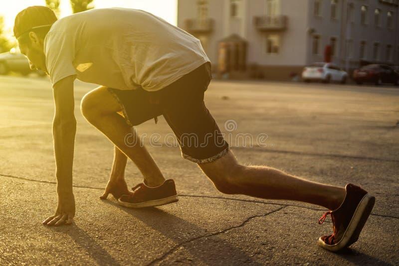 Vue arrière d'athlète de jeune homme en silhouette occasionnelle fonctionnant dans la ville urbaine sur un coucher du soleil images libres de droits