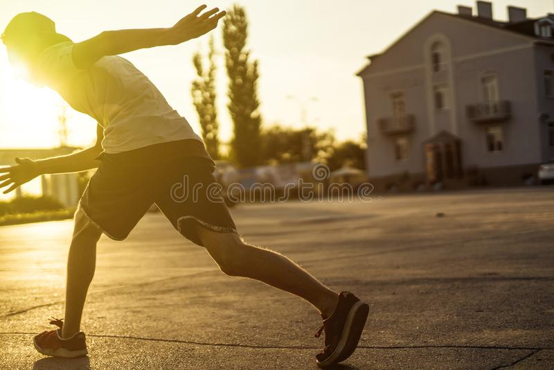 Vue arrière d'athlète de jeune homme en silhouette occasionnelle fonctionnant dans la ville urbaine sur un coucher du soleil photographie stock