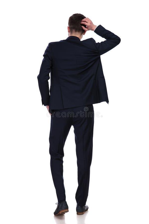 Vue arrière d'homme d'affaires rayant sa tête et pensée photographie stock