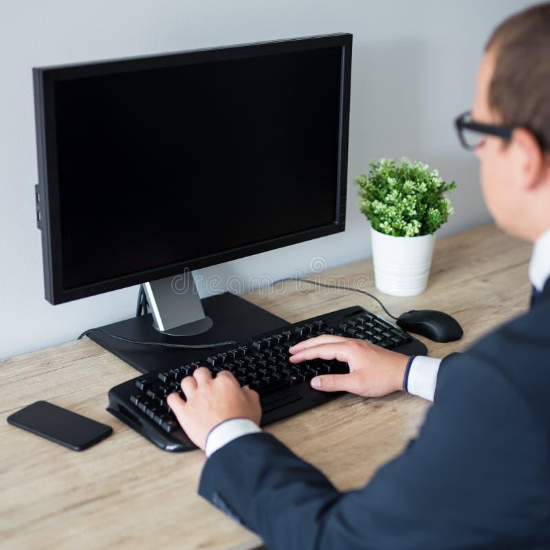 Vue arrière d'homme d'affaires utilisant l'ordinateur dans le bureau - l'espace de copie sur l'écran vide images libres de droits