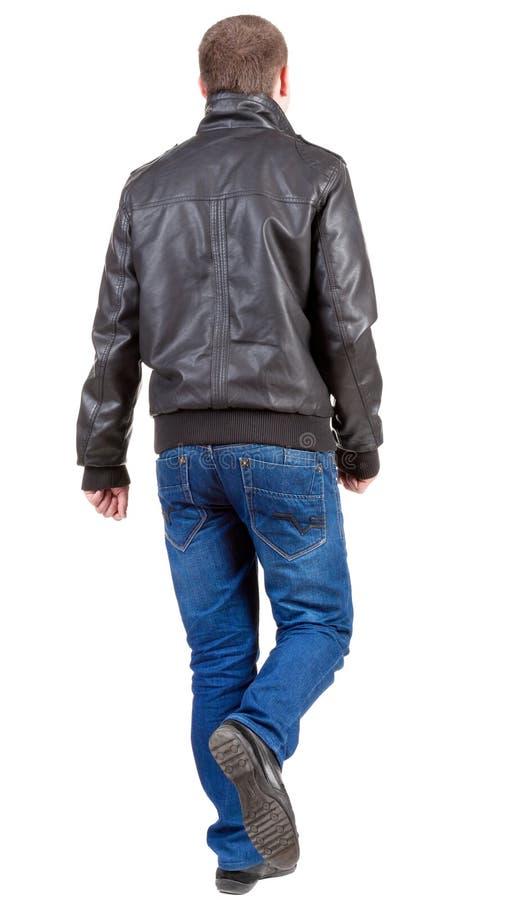 Vue arrière d'homme bel allant dans la veste.  jeune type de marche i photographie stock