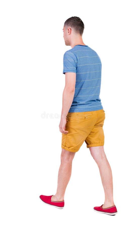 Vue arrière d'homme bel allant en bref jeune type de marche photo libre de droits